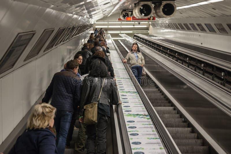 Folk som går upp från en tunnelbanastation av Budapest på en rulltrappa på rusningstider royaltyfri foto