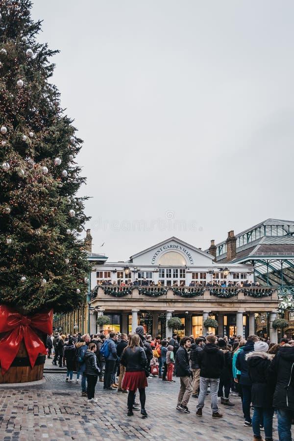 Folk som går vid den jätte- julgranen i den Covent Garden marknaden, London, UK royaltyfria bilder