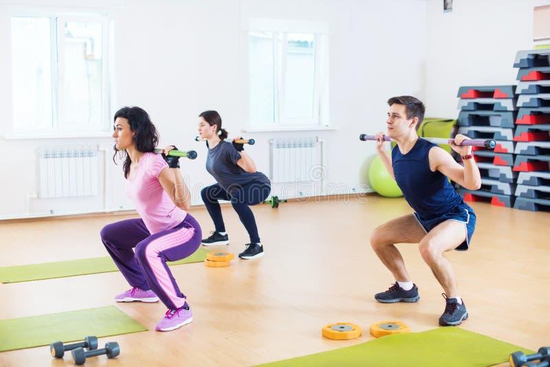 Folk som gör squats med skivstånger på skuldror som övar på konditionklubban arkivfoton