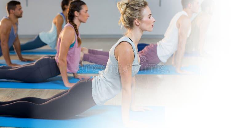 Folk som gör yoga på golv i idrottshall royaltyfria bilder