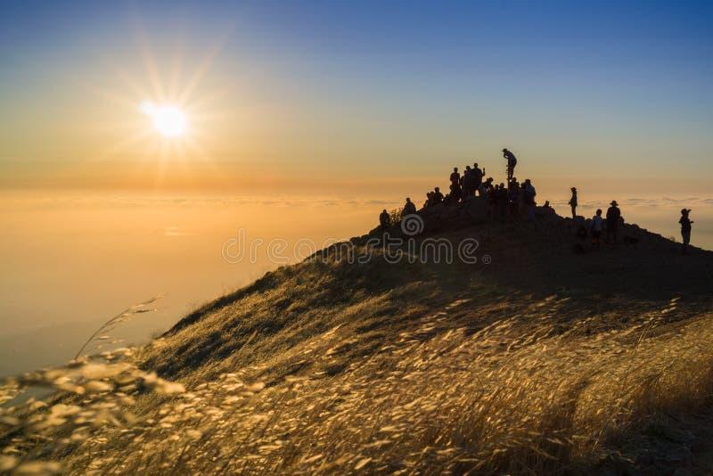 Folk som håller ögonen på en färgrik solnedgång över ett hav av moln royaltyfri fotografi