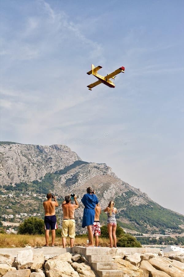 Folk som håller ögonen på och gör foto av brandmanflygplanet i handling royaltyfri fotografi