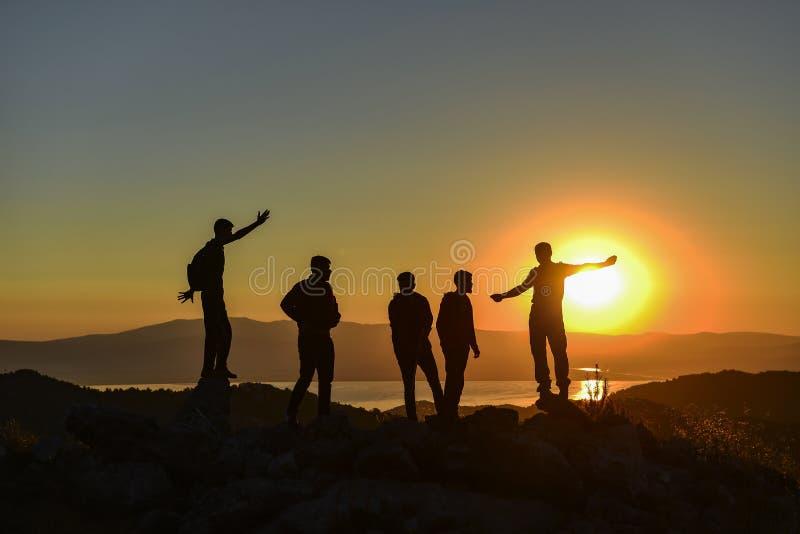 Folk som håller ögonen på soluppgången på toppmötet royaltyfria foton