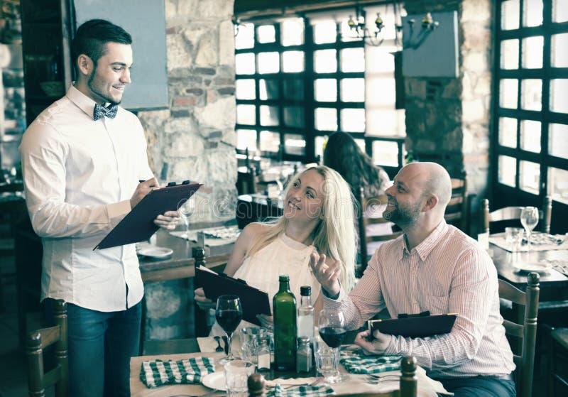 Folk som har den lantliga restaurangen för matställe royaltyfri bild
