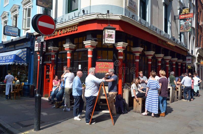 Folk som har en stång för drinkyttersidaengelska i Sohoen, London UK royaltyfria foton