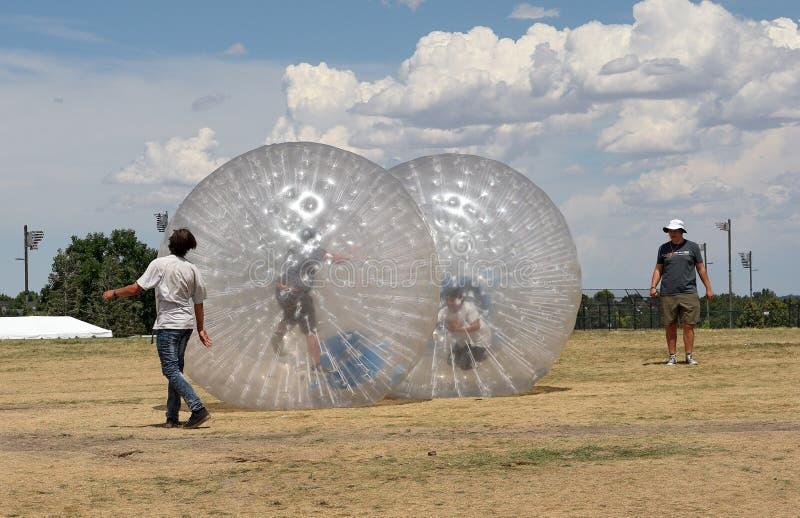 Folk som har fanen med Zorbing bollar på Colorado den irländska festivalen arkivfoton