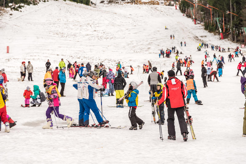 Folk som har gyckel på snöig berghimmelsemesterort royaltyfria bilder