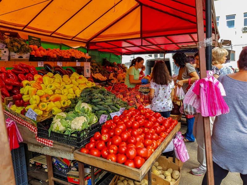 Folk som köper nya frukter och grönsaker på den lokala marknaden fotografering för bildbyråer
