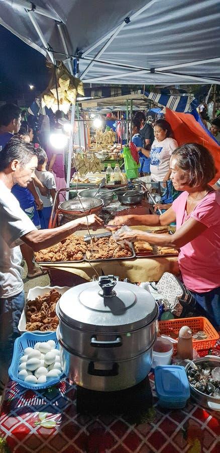 Folk som köper och säljer gatamat på en nattmarknad nära Oslob Visayas Filippinerna royaltyfri fotografi