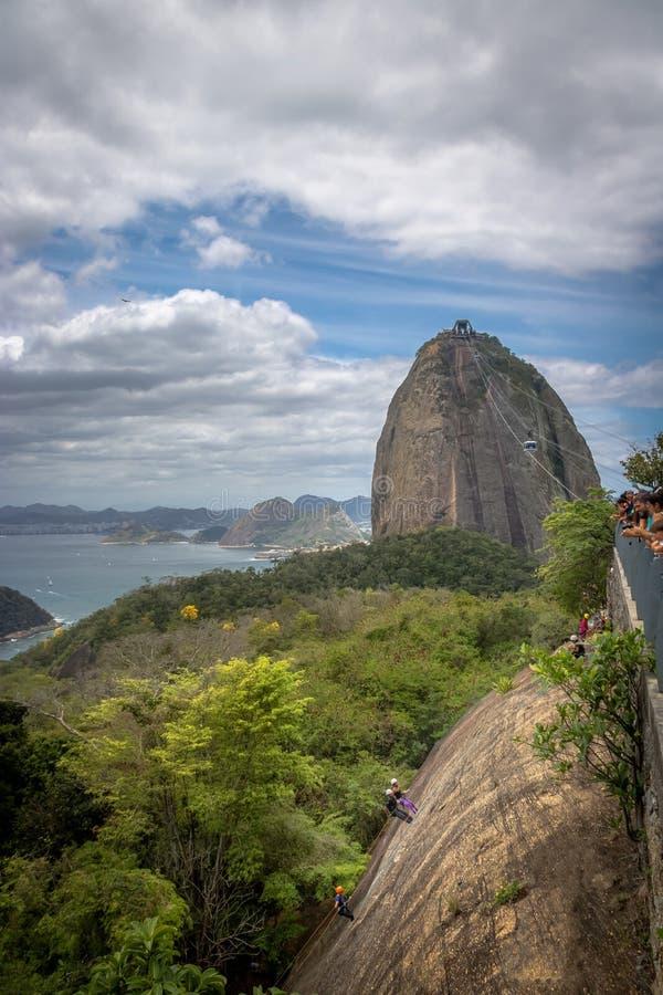Folk som klättrar den Urca kullen med Sugar Loaf Mountain på bakgrund - Rio de Janeiro, Brasilien fotografering för bildbyråer