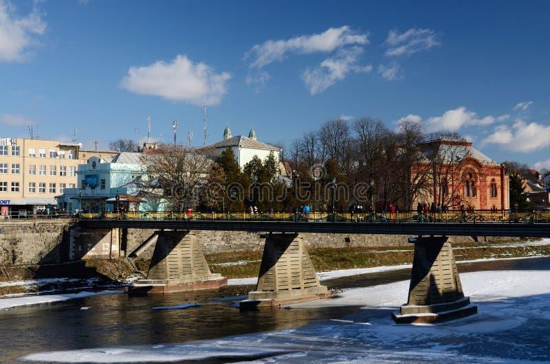 Folk som korsar den gamla fot- bron över den Uzh floden i Uzhhorod, västra Ukraina arkivfoton