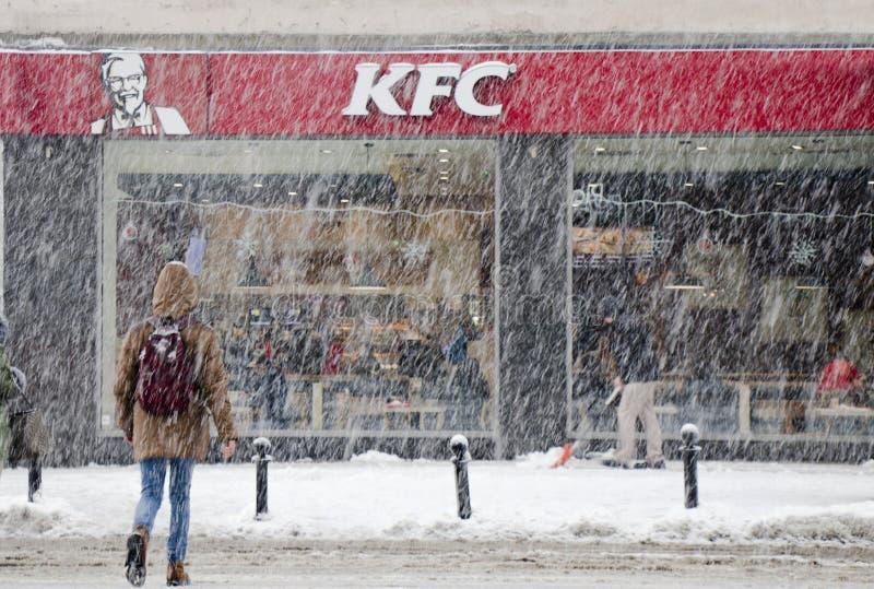 Folk som korsar den snöig stadsgatan i tungt snöfall in mot KFC snabbmatrestaurang royaltyfria foton