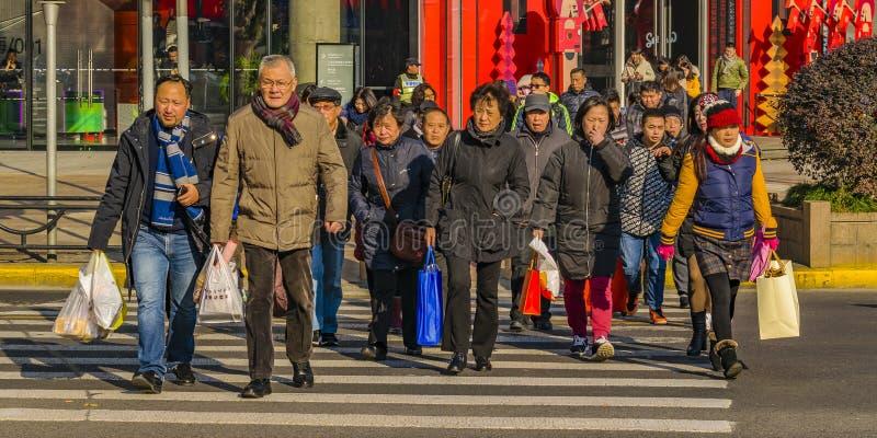Folk som korsar gatan, Shanghai, Kina royaltyfria foton