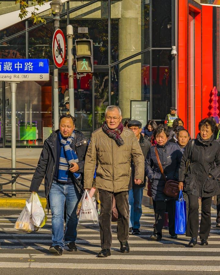Folk som korsar gatan, Shanghai, Kina fotografering för bildbyråer