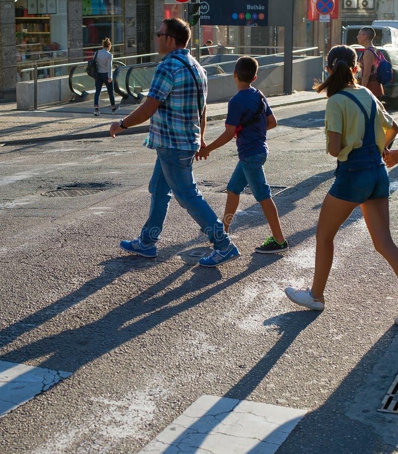Folk som korsar vägen Porto Portugal arkivfoto