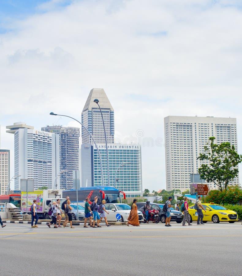 Folk som korsar vägen Singapore arkivfoton