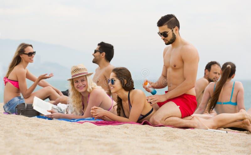 Folk som lägger på sand på stranden arkivfoto