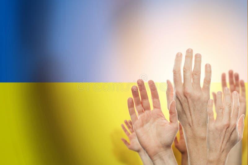 Folk som lyfter händer och flaggan Ukraina på bakgrund Patriotiskt begrepp royaltyfri bild