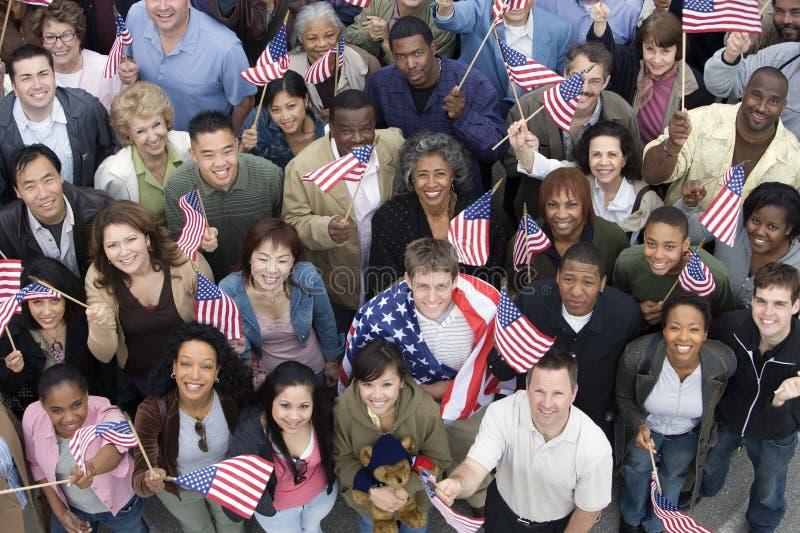 Folk som lyfter tillsammans amerikanska flaggan royaltyfria bilder