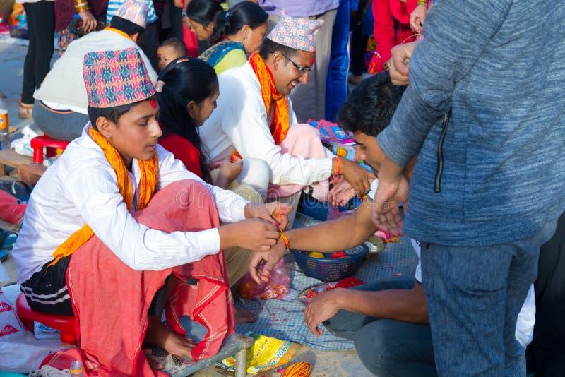 Folk som mottar Rakshya Bandhan från brahmanprästerna på Januari arkivfoton