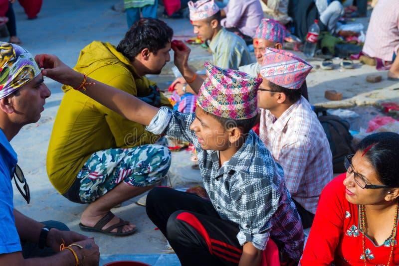 Folk som mottar Rakshya Bandhan från brahmanprästerna på Januari arkivfoto