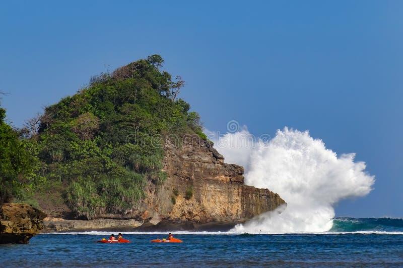 Folk som paddlar på kajaken i lagun på bakgrund för avbrottsvågor royaltyfri fotografi