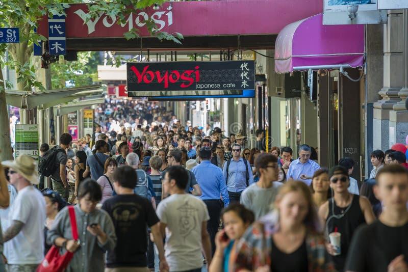Folk som promenerar en upptagen gata i Melbourne royaltyfria foton