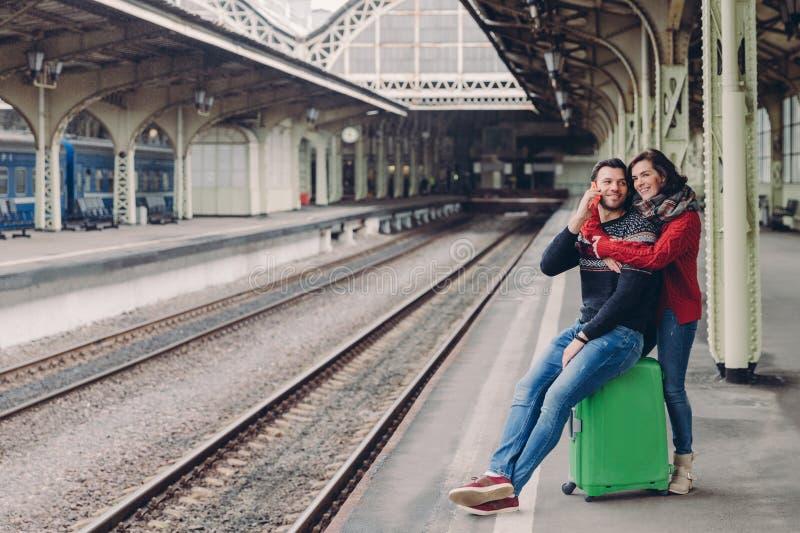 Folk som reser, förhållandebegrepp Den lyckliga orakade make- och fruomfamningen på järnvägsstationen som går att ha tur, har royaltyfri bild