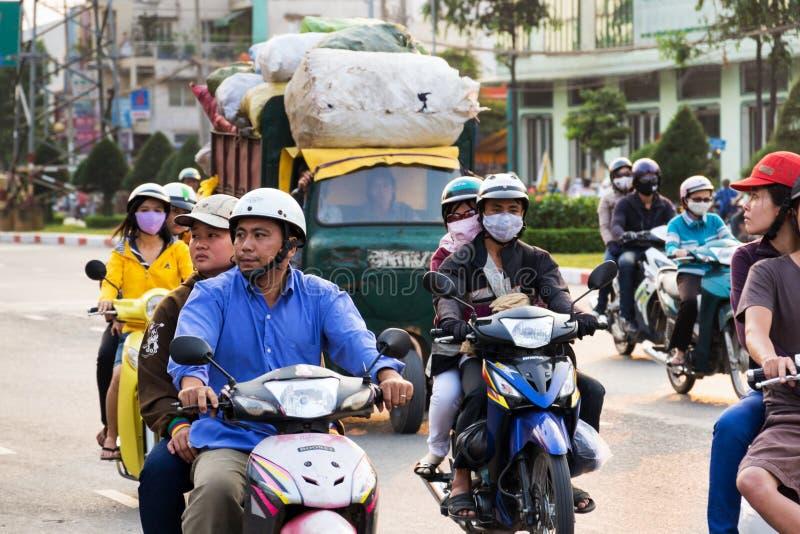 Folk som rider sparkcyklar på en upptagen gata i Ho Chi Minh City, Vietnam arkivbilder