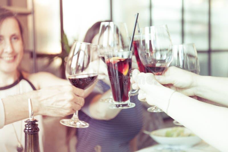 Folk som rostar med exponeringsglas av rött vin, closeup arkivfoto