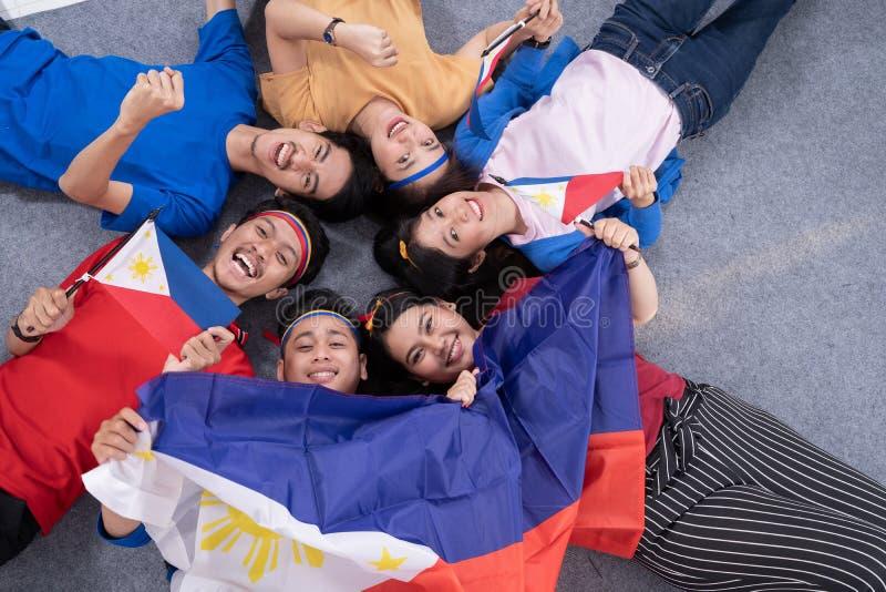 Folk som rymmer den philippines flaggan som firar sj?lvst?ndighetsdagen arkivfoton