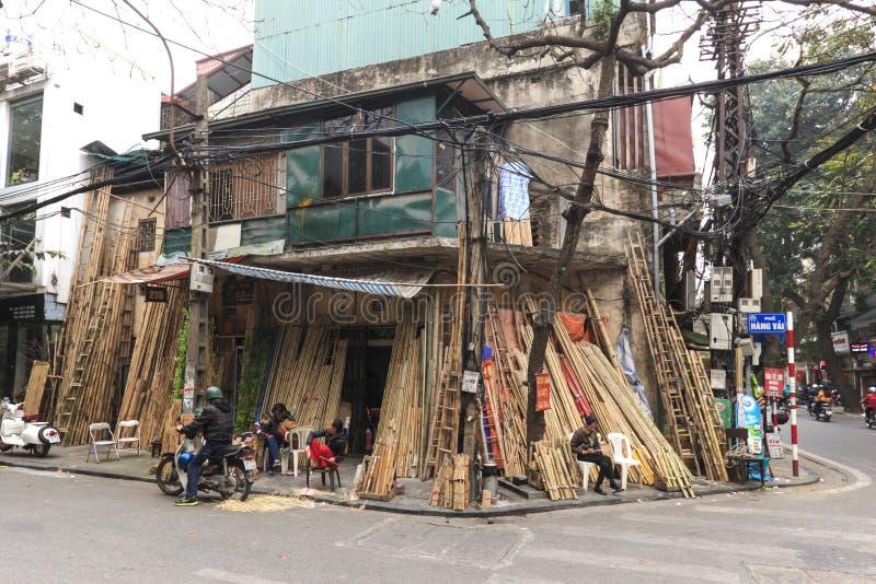 Folk som säljer bambuhjälpmedel i den gamla staden på Hanoi arkivfoto