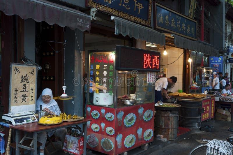 Folk som säljer mat i en gatamarknad på den muslimska fjärdedelen i staden av Xian i Kina arkivbilder