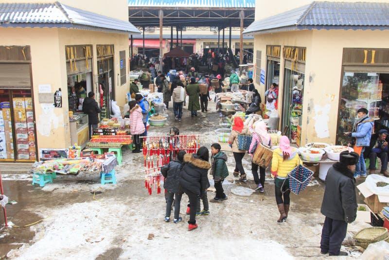 Folk som säljer och köper i en lokal kinesisk marknad arkivbilder