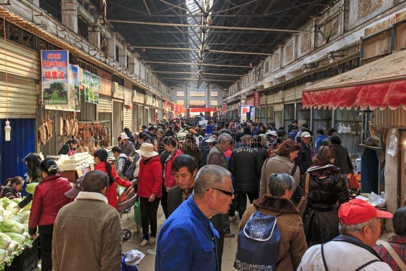 Folk som säljer och köper i en traditionell marknad i mitten av Kunming arkivbilder