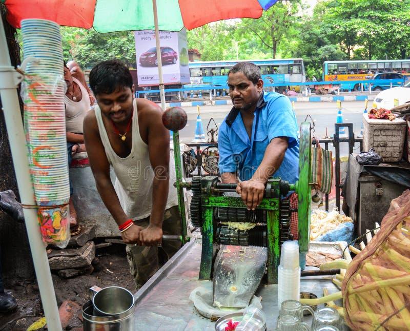 Folk som säljer sockerrörfruktsaft på marknaden i Kolkata, Indien arkivbild