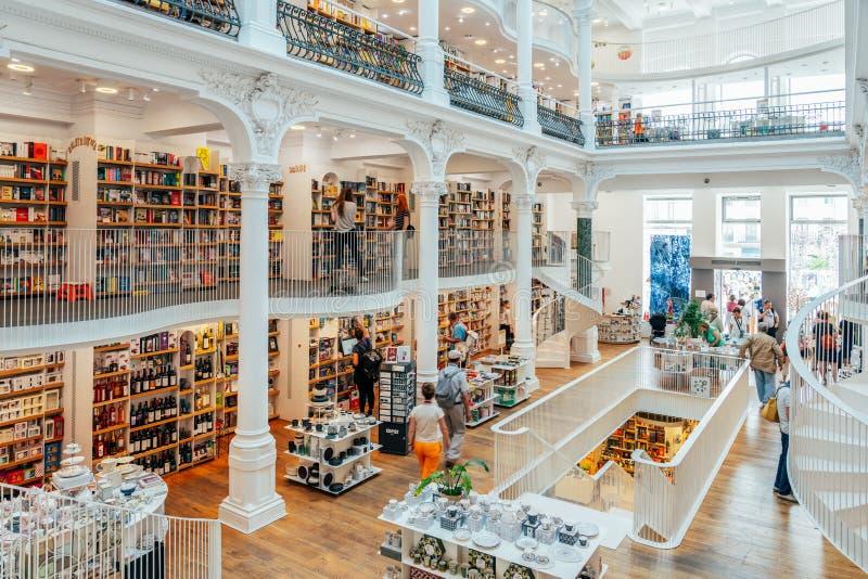 Folk som söker efter en bred variation av böcker som är till salu i härligt arkivboklager royaltyfri bild