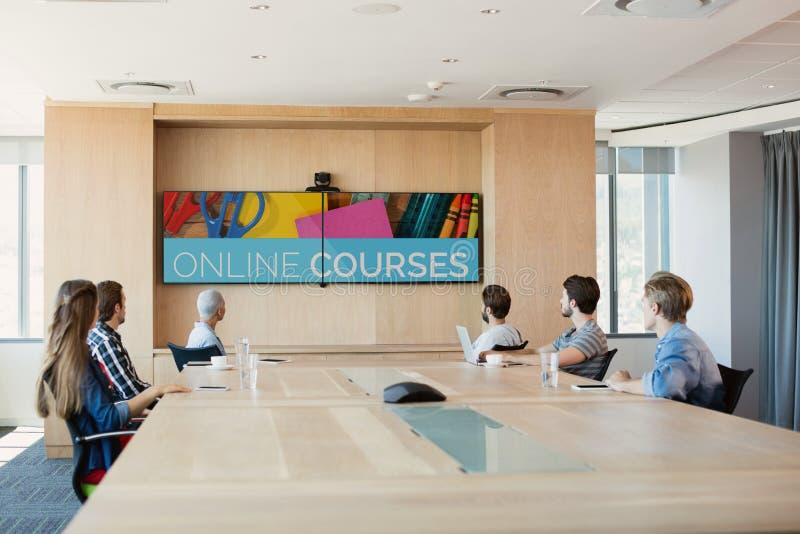 Folk som ser en TV med e-lärande information i skärmen royaltyfria foton
