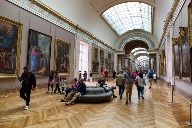 Folk som ser målningar i Louvremuseet royaltyfri foto