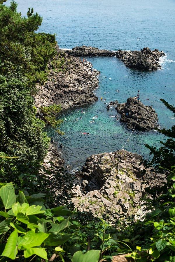 Folk som simmar och snorklar längs kustlinjen av Seogwipo, Jeju ö, Korea royaltyfria bilder