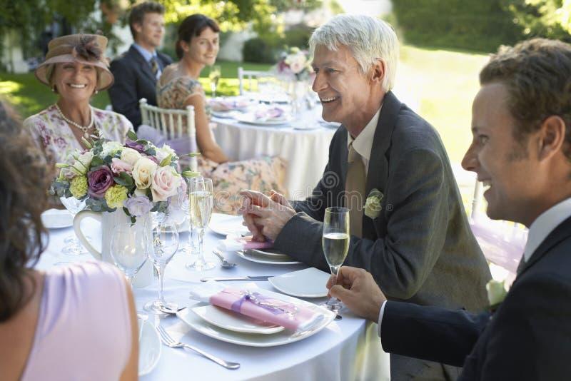 Folk som sitter på brölloptabeller arkivfoto