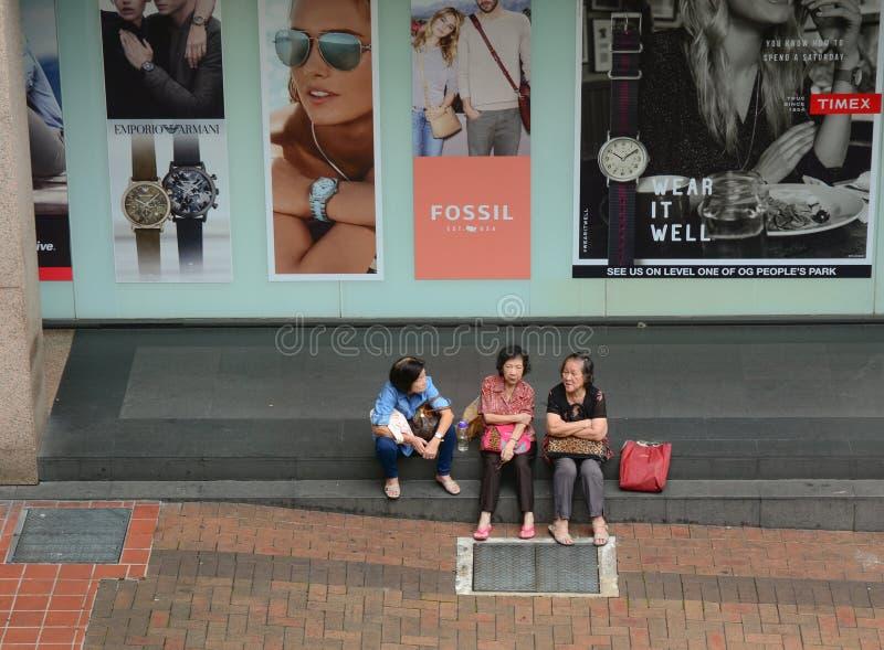Folk som sitter på gatan arkivbilder