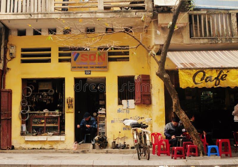 Folk som sitter på gatan på centret i Hanoi, nordliga Vietnam royaltyfria bilder