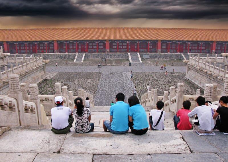 Folk som sitter på trappa i Forbidden City och ser att att närma sig för stormar royaltyfria foton
