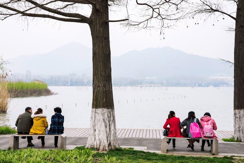 Folk som sitter vid Xuanwu sjön royaltyfria bilder