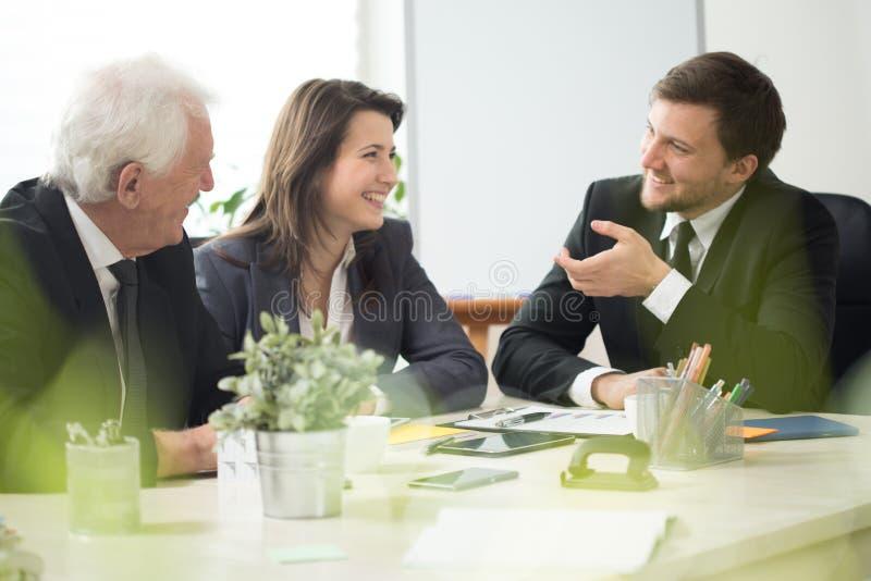 Folk som skrattar under affärstidsbeställning arkivfoto