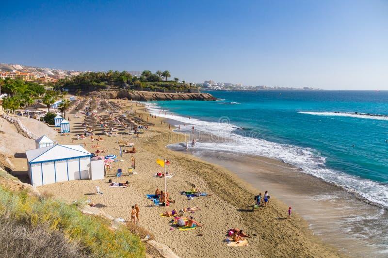 Folk som solbadar på den sceniska stranden royaltyfria foton