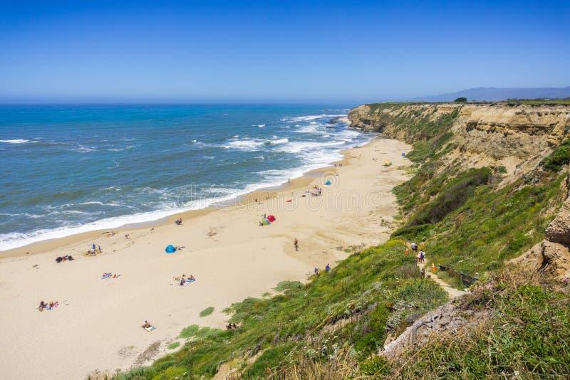 Folk som solbadar på en sandig strand på Stilla havetkustlinjen arkivfoto