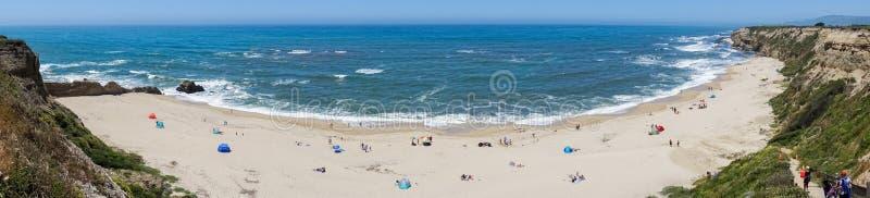 Folk som solbadar på en sandig strand på Stilla havetkustlinjen royaltyfri bild