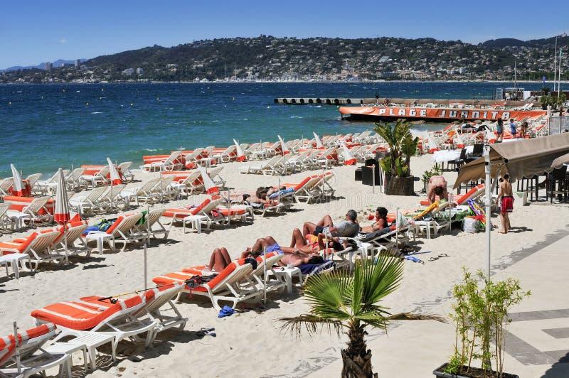 Folk som solbadar på stranden i Juan-Les-ben, Frankrike fotografering för bildbyråer